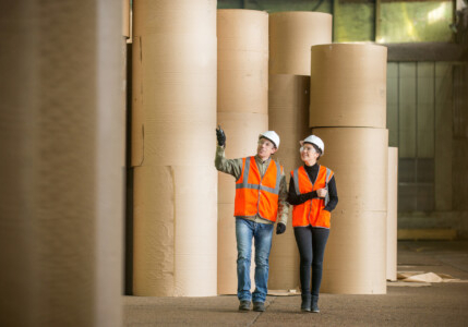 two people in high vis clothing walking through a papermaking facility paper industry