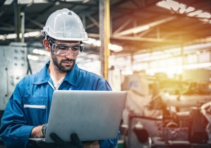 Confident Engineer In Blue Jumpsuit Holding Laptop Computer In A Warehouse.